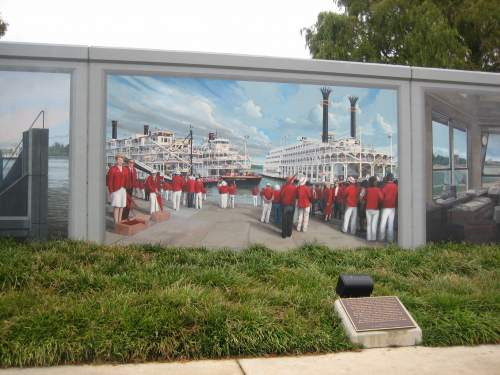 floodwall mural of ambassadors greeting three queens